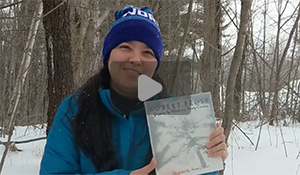 Jessica is standing in snow-filled woods with a copy of the book